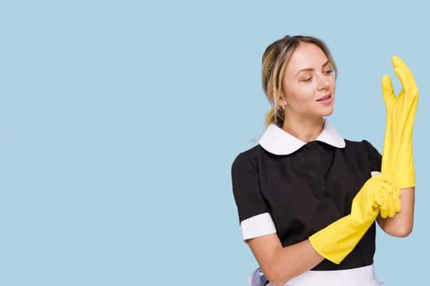 attractive-young-woman-wearing-yellow-glove-against-blue
