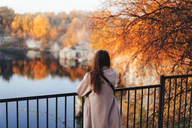 Autumn girl standing backwards watching nature
