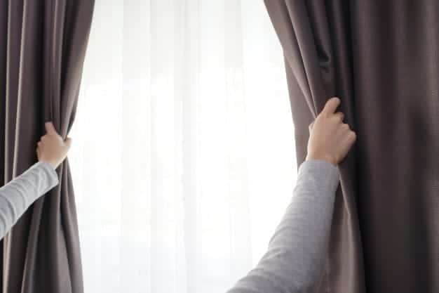 Closeup women hand opening curtain