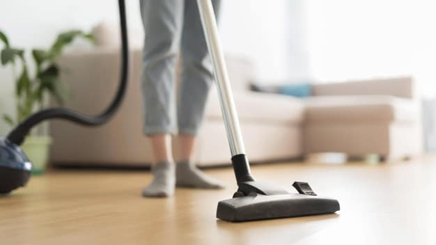front-view-woman-using-vacuum-cleaner-room