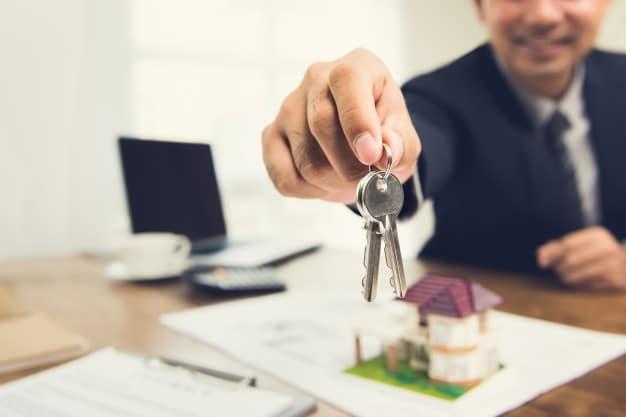 smiling-businessman-as-real-estate-broker-agent-givng-house-keys