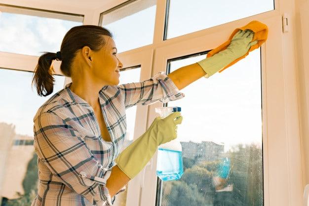 woman-housekeeper-cleaning-windows