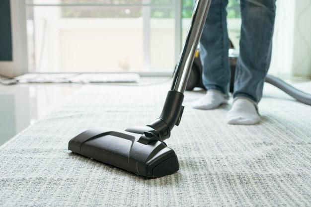 women-using-vacuum-cleaner-cleaning-carpet-living-room