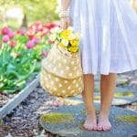 A lady standing barefoot with a basket of flowers on a sunny day.