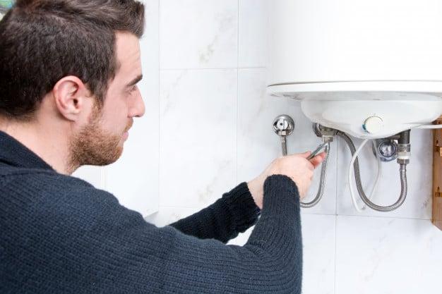 Plumber fixing electric water heater