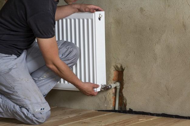Professional plumber installing heating radiator