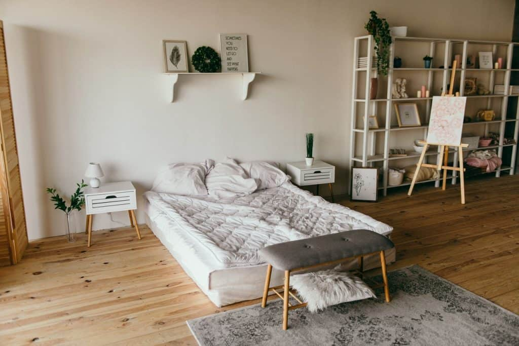 A bedroom with a white wooden shelf beside the bed