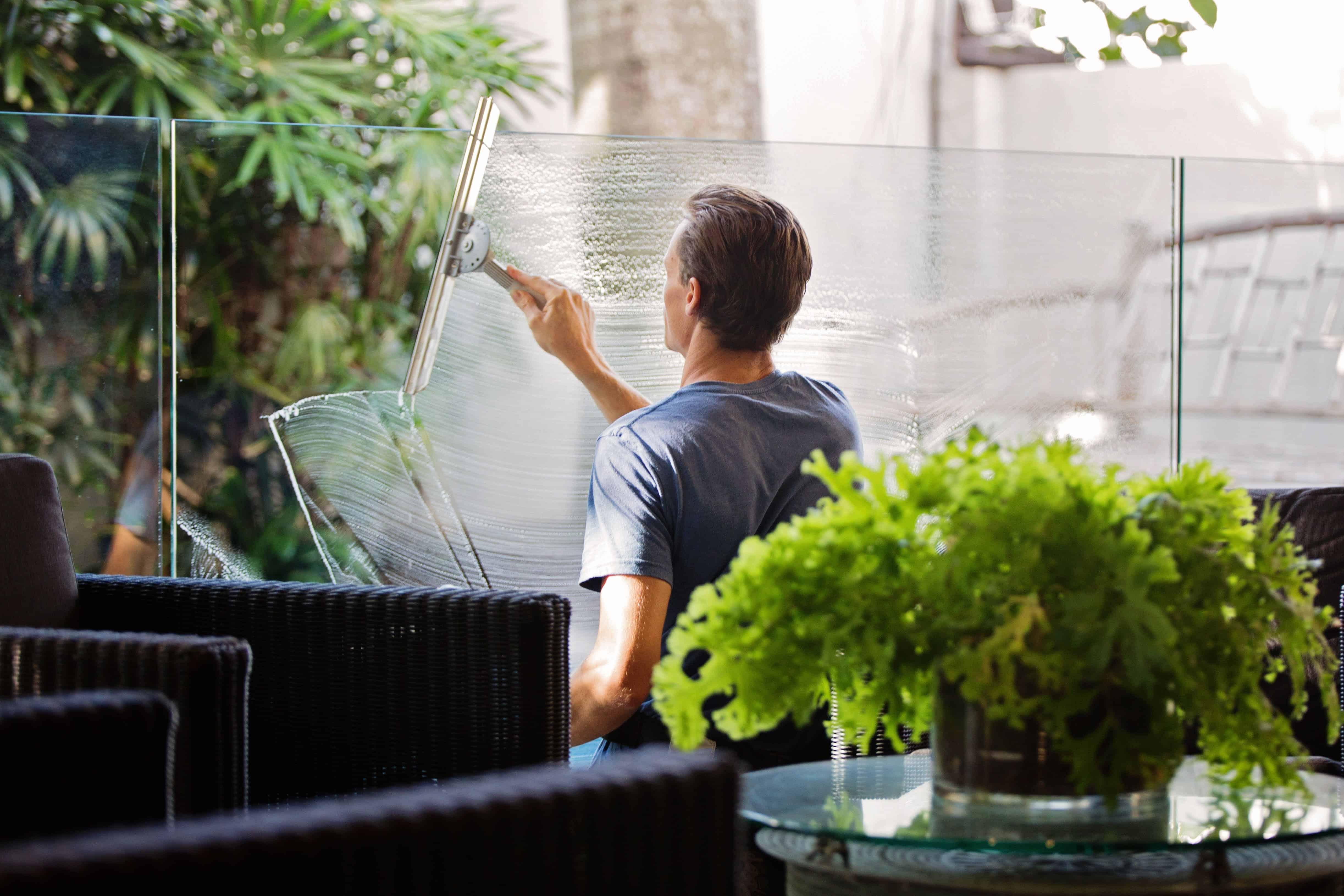 man-in-gray-shirt-cleaning-clear-glass-wall-near-sofa-713297-min