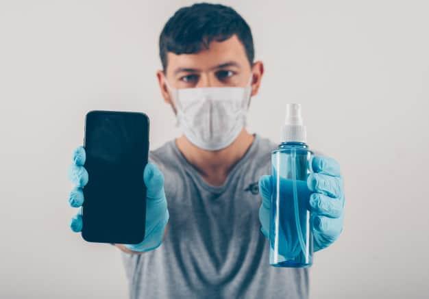 man holding phone hand sanitizer medical gloves mask