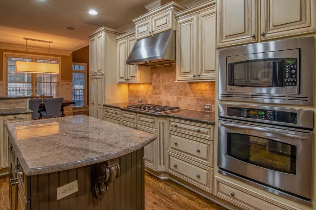 A modern kitchen with stainless steel microwave, stove, and oven