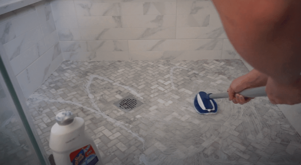 A person cleaning mould from a shower floor