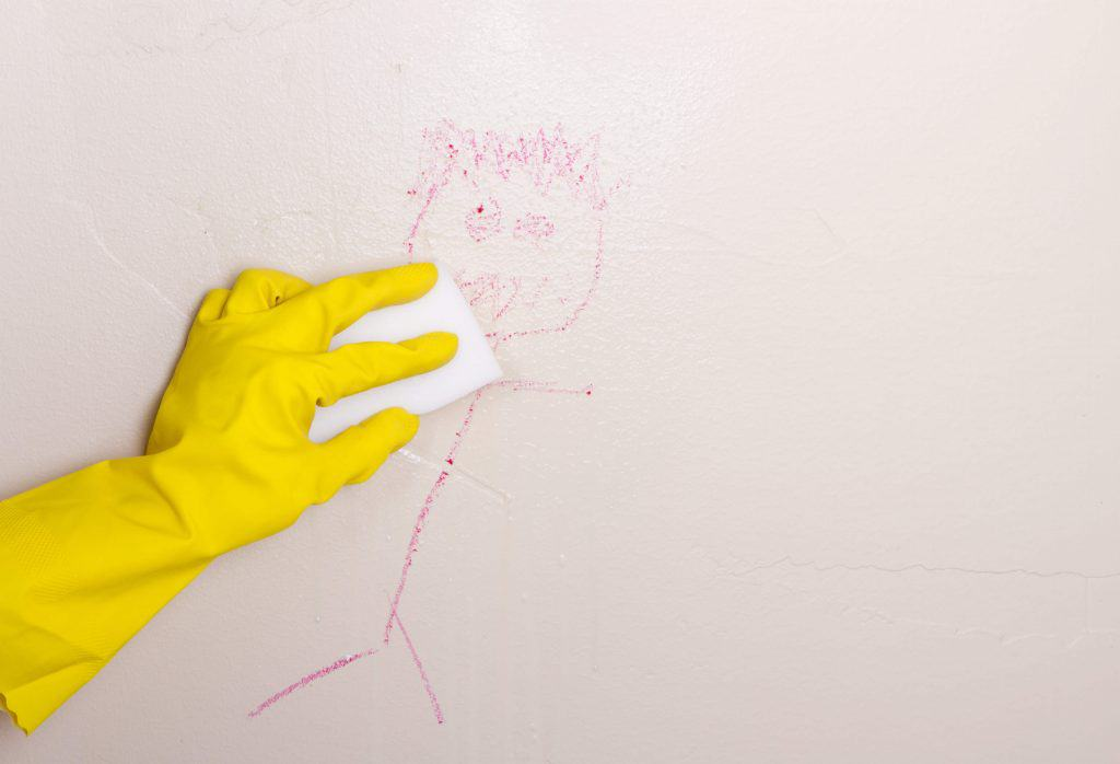 Person with yellow rubber glove cleaning drawing on wall