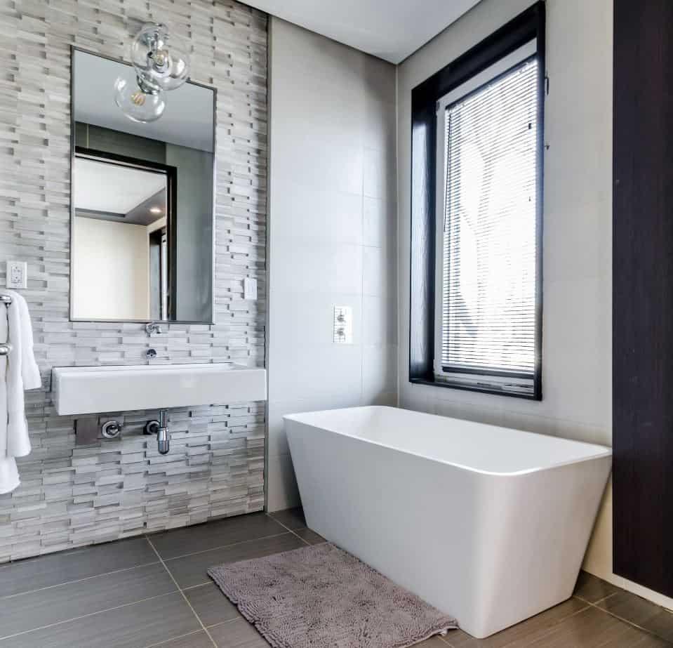 Large white rectangular bathtub in a modern bathroom