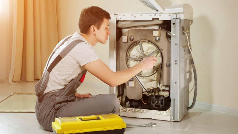 Man fixing a top load washing machine