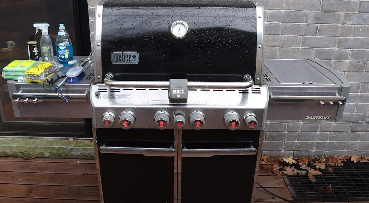 large Weber barbeque grill with cleaning products sitting on the side