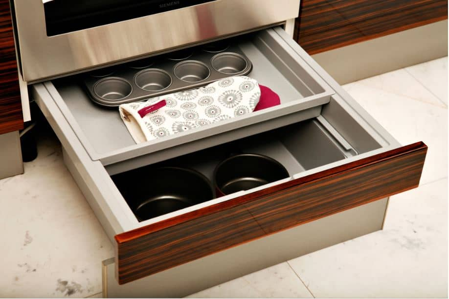 Wooden kitchen cabinets filled with baking trays