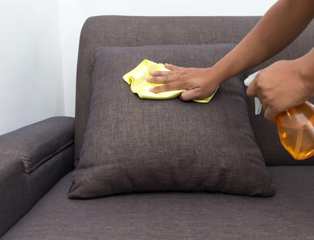 person scrubbing upholstered pillow with a cleaning solution