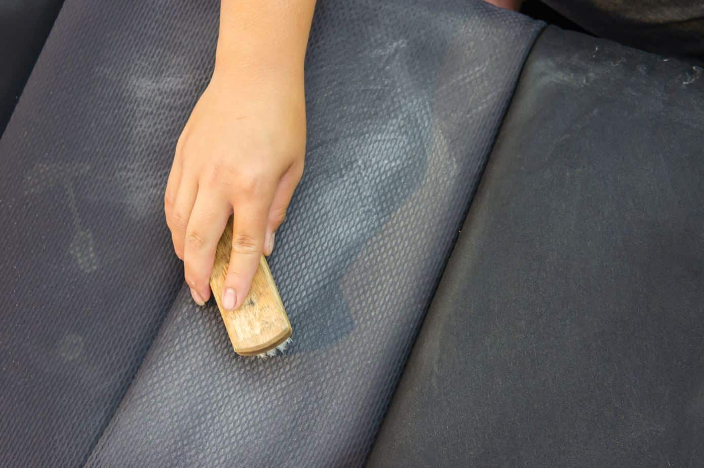 woman scrubbing an upholstered seat with a hard brush