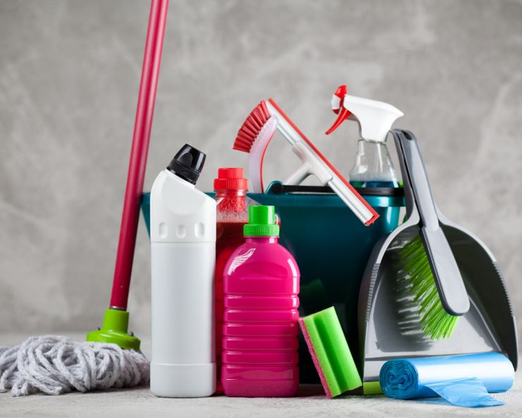 assorted cleaning tools and equipment on the floor including a mop, dustpan, bucket and various coloured spray bottles