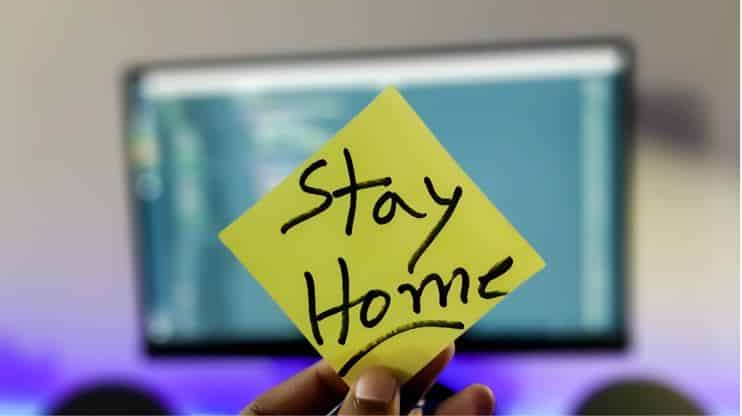 person holding up post-it note that says 'stay home'