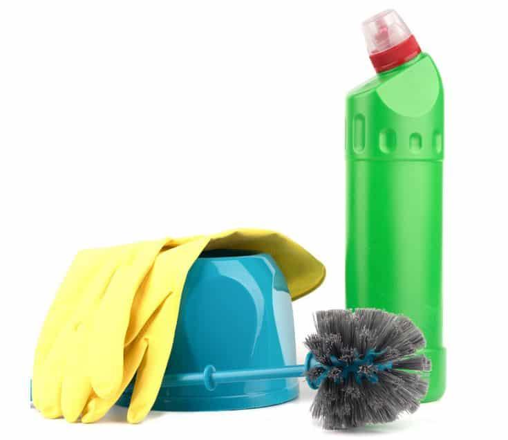 yellow gloves draped over blue toilet brush and toilet brush holder